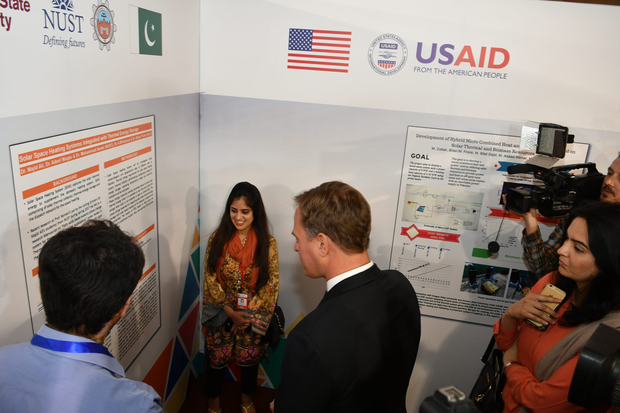 Fareeha Ahmad, a student from NUST discusses the Solar Space Heating Systems Integrated with Thermal Energy Storage joint research project with Dr. Christopher Steel, the USAID/Pakistan Education Director, at the first USPCASE Research Expo.